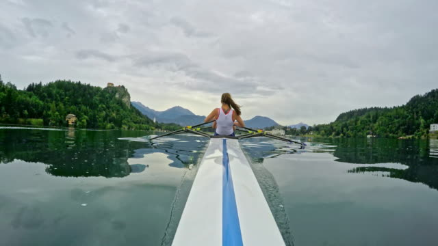 pov female athlete sculling on a lake viewed from the bow - scull stock videos & royalty-free footage