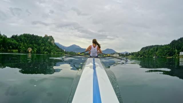 vídeos y material grabado en eventos de stock de atleta femenina de pov remar en un lago visto desde la proa - remo con espadilla