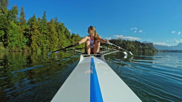 pov female athlete sculling on a sunny lake in a double scull - canottaggio senza timoniere video stock e b–roll