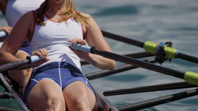 female athlete sculling with team mate in a double scull on a sunny day - rowing stock videos & royalty-free footage