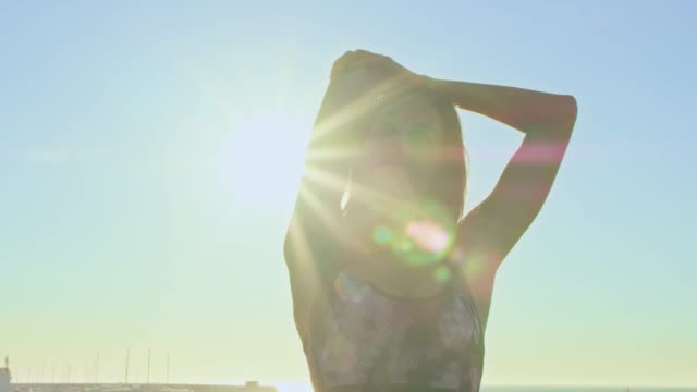 female athlete stretching arm during sunset - sports bra stock videos & royalty-free footage