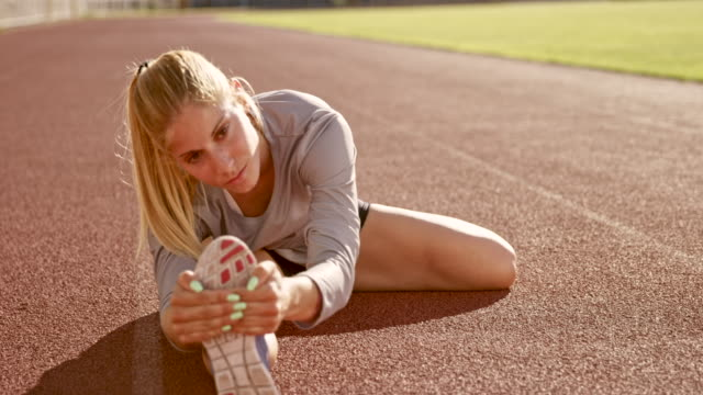 slo mo female athlete stretching her legs while sitting on the track in the stadium - image focus technique stock videos & royalty-free footage