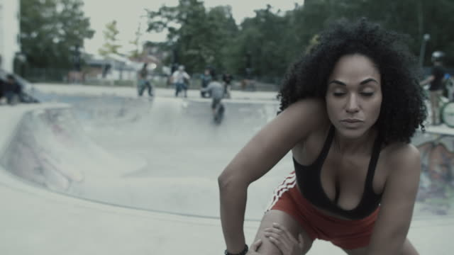 Female athlete stretching/warming up in front of Skateboard park in urban setting in Berlin, Germany.