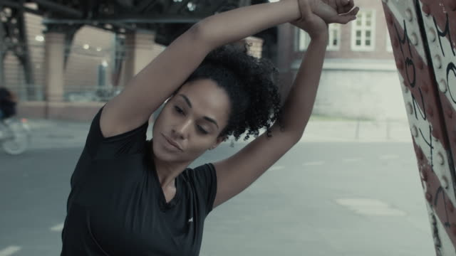 female athlete stretching/warming up in urban setting in berlin, germany. - warming up stock videos and b-roll footage