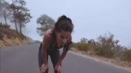 Female athlete taking breath from running
