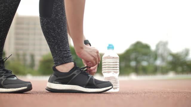 female athlete tying on sports shoe - tying stock videos & royalty-free footage