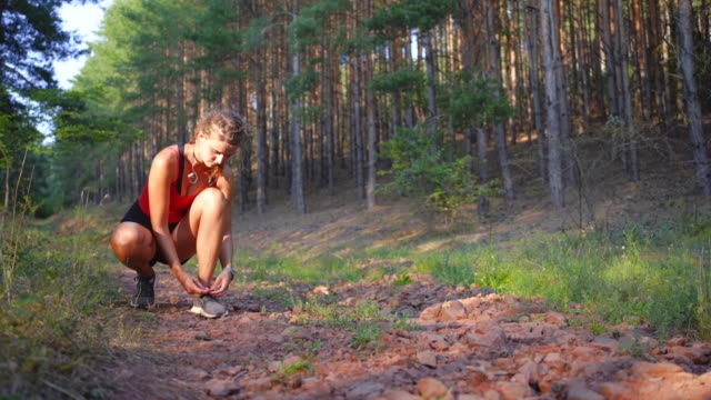 female athlete tying on sports shoe - cross country running stock videos & royalty-free footage
