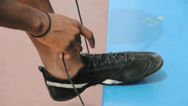 CU HA Female athlete tying shoelaces, Los Angeles, California, USA