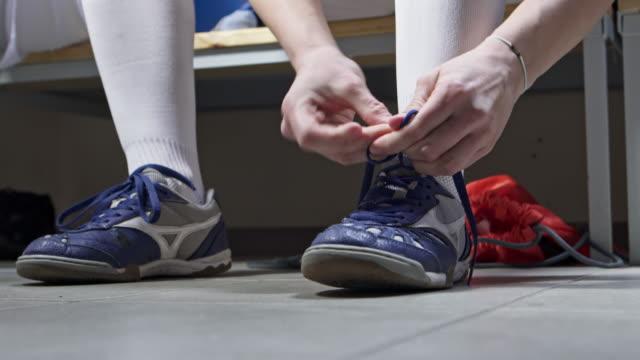 CU female athlete tying shoelaces