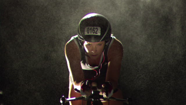 MS SLO MO Female athlete wearing helmet on racing bicycle stretching hands with mist falling around / Los Angeles, California, United States