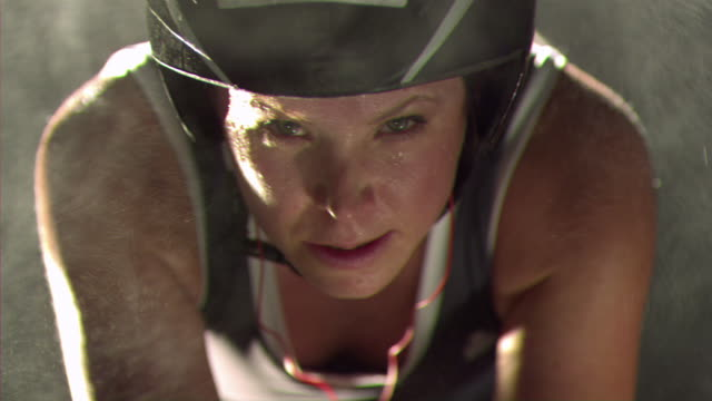 CU SLO MO Female athlete wearing helmet on racing bicycle with mist falling around / Los Angeles, California, United States