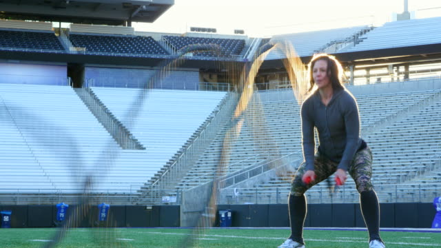 ms female athlete working out with battle rope exercise during training session on field in stadium - ロープ点の映像素材/bロール