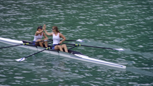 female athletes doing high five in their double scull on a sunny lake - scull stock videos & royalty-free footage
