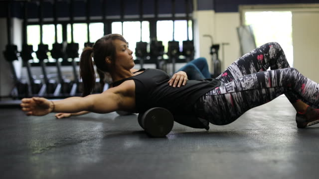 vídeos de stock e filmes b-roll de female athletes exercising on foam rollers in gym - rolar