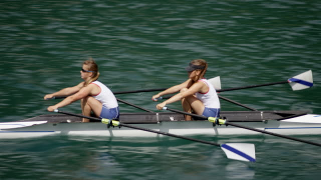female athletes gliding across a sunny lake in a double scull - scull stock videos & royalty-free footage