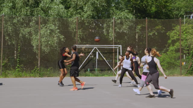 female athletes playing streetball on sunny day - basketball sport stock videos & royalty-free footage