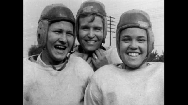 vidéos et rushes de / female athletes recovering after football game / coach talks to seated women / women laughing and smiling play regulation football all female... - 1934