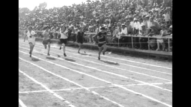MS female athletes run dash past audience in bleachers toward camera / slow motion shot of athletes crossing finish line / MS slow motion Elizabeth...