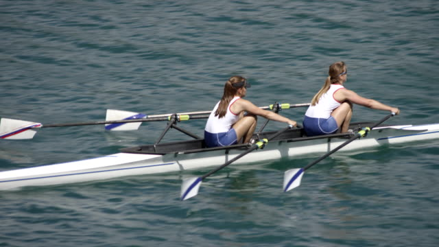 female athletes sculling across a sunny lake in a double scull - rowing stock videos & royalty-free footage