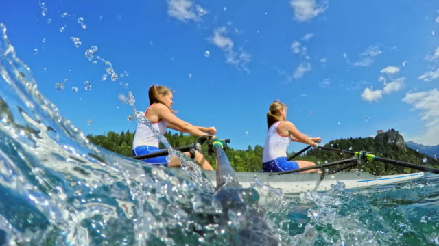 pov female athletes sculling on a lake viewed from the oar striking the water - canottaggio senza timoniere video stock e b–roll