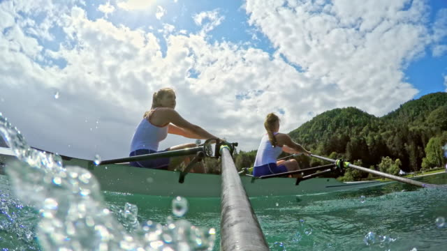 pov female athletes sculling on a lake viewed from the shaft of the oar - canottaggio senza timoniere video stock e b–roll