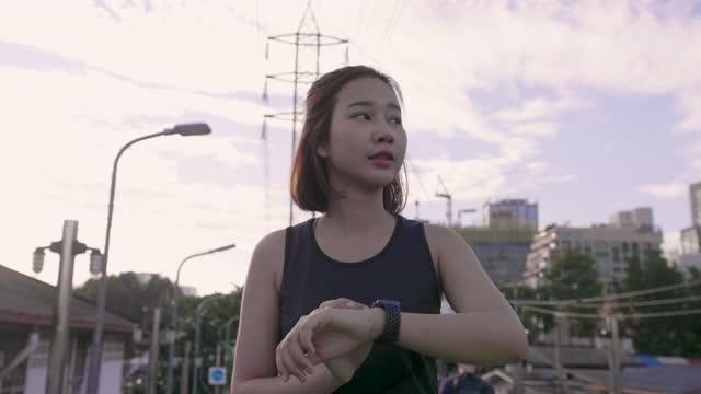 stockvideo's en b-roll-footage met vrouwelijke atleten die slimme horloges gebruiken bij de stad van de rivier - jogster