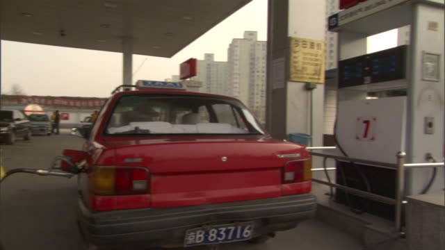 ms pan female attendant refueling taxi at lpg filling station, driver getting out of taxi, beijing, china - filling station attendant stock videos & royalty-free footage