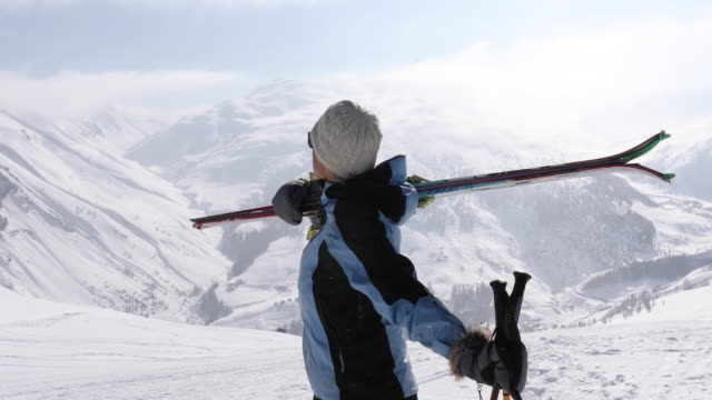 Female backcountry skier ascends snow slope above mountains