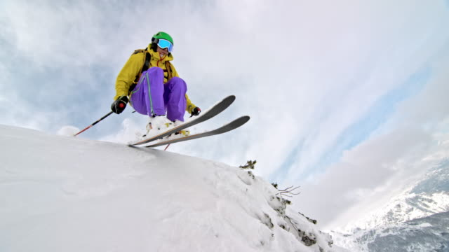 SLO MO Female backcountry skier jumping in deep powder