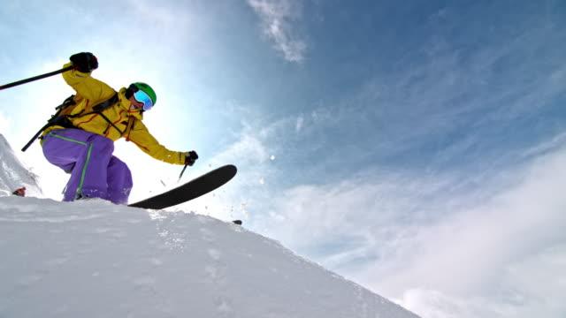 slo mo weibliche backcountry-skifahrerin springt von einem felsen - freistil skifahren stock-videos und b-roll-filmmaterial