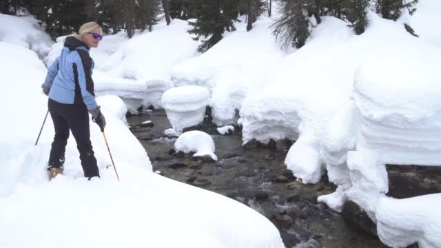 vídeos y material grabado en eventos de stock de travesía femenina esquiador pausas por nevadas creek - chaqueta de esquiar