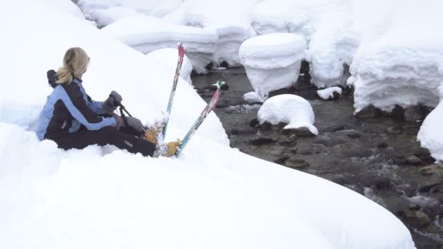 female backcountry skier pauses by snowy creek - ski jacket stock videos & royalty-free footage
