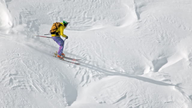 SLO MO Female backcountry skier skiing down the mountain slope