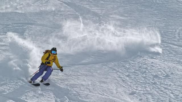 slo mo kvinna backcountry skidåkning ridning ner för berget - freestyleskidåkning bildbanksvideor och videomaterial från bakom kulisserna