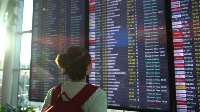 female backpacker at the airport looking at the boarding schedule ready to travel - nomadic people stock videos & royalty-free footage