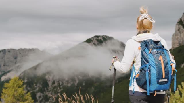 stockvideo's en b-roll-footage met slo mo vrouwelijke backpacker die van het bergmening geniet - julian alps