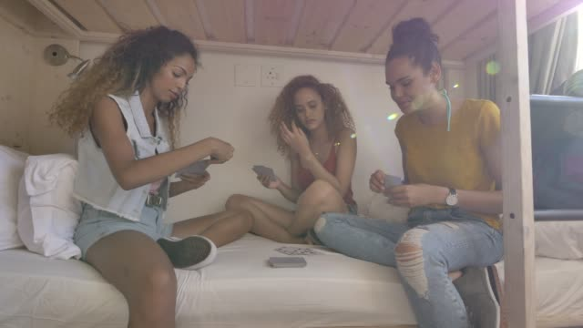 vídeos de stock e filmes b-roll de female backpackers playing cards on bunkbed - carta de baralho