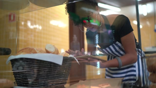 female baker checking breads in the bakery - bakery stock videos & royalty-free footage