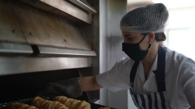 female baker removing fresh breads from the oven with face mask - safety stock videos & royalty-free footage