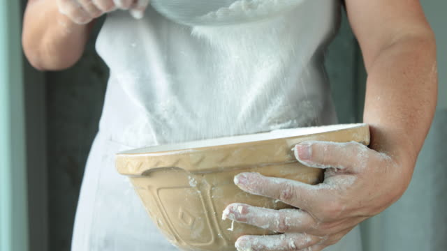 MS female baker sifting flour into bowl