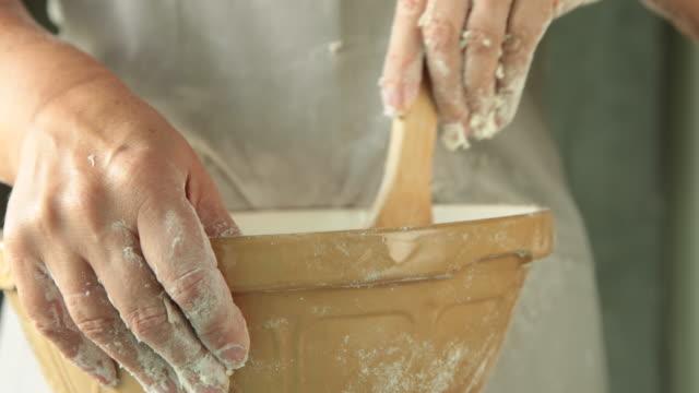 CU female baker stiring mixture in bowl