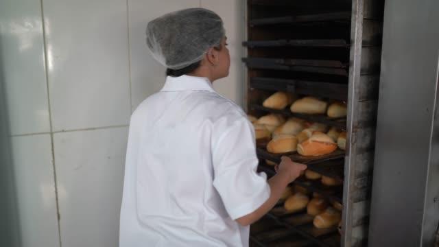 オーブンから焼きたてのパンを取り出す女性パン屋 - オーブンの天板点の映像素材/bロール