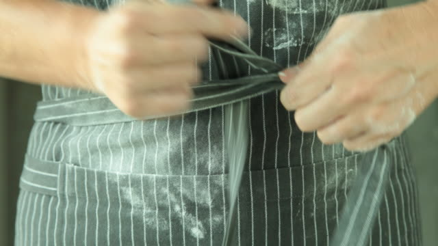 cu female baker tying bow at front of apron - apron stock videos & royalty-free footage