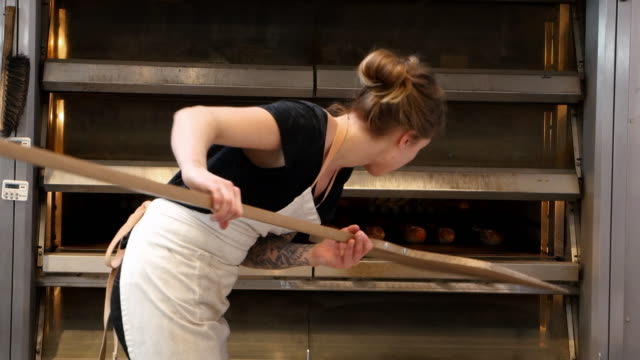 ms female baker using peel to arrange freshly baked baguettes in oven in bakery - baker occupation stock videos and b-roll footage