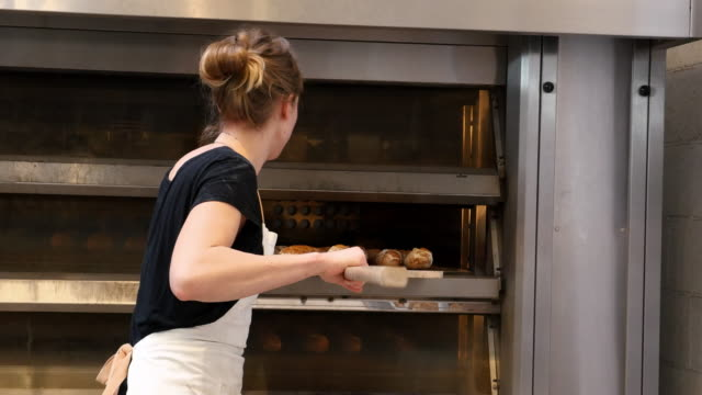 ms female baker using peel to move freshly baked baguettes from oven to cooling rack in bakery - peel stock videos & royalty-free footage