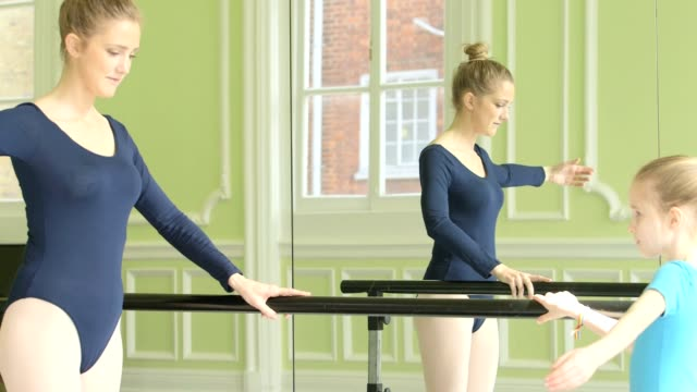 Female Ballet Dancer and Yuong Ballerina face each other on the training barre and practice movements