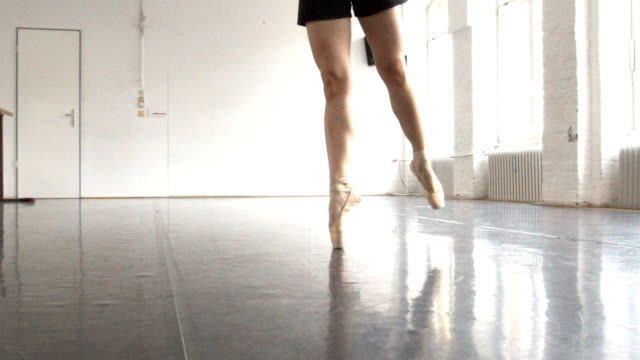 female ballet dancer dancing on tiptoes in rehearsal room - ballet shoe stock videos and b-roll footage