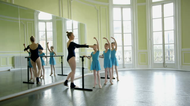 female ballet dancer encourages arm and leg extension in three youg ballerinas as they balance on the barre - barre stock videos & royalty-free footage