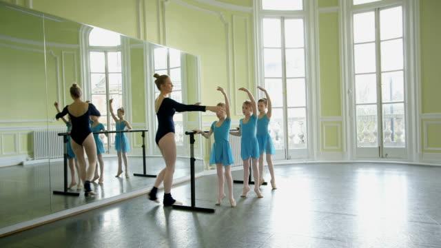 female ballet dancer encourages arm and leg extension in three youg ballerinas as they balance on the barre - auf den zehenspitzen stock-videos und b-roll-filmmaterial