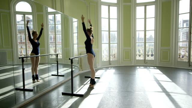 mls female ballet dancer faces mirror and practices her movements - auf den zehenspitzen stock-videos und b-roll-filmmaterial